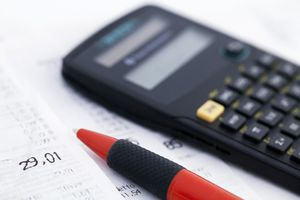 A calculator and a pen on accounting documents.