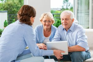 A couple having meeting with financial advisor or insurance agent at home.