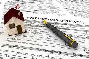 House-shaped paperweight and pen on mortgage loan application form