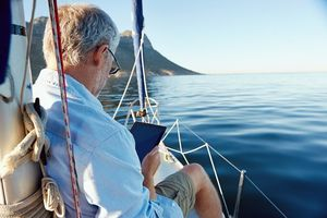 Retiree reading in a boat on the water