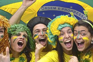 A group of young adults dressed up, probably for a soccer match, wearing the colors of Brazil and waving a Brazilian flag.