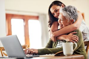 Shot of a young woman hugging her grandmother helping her with her on a laptop