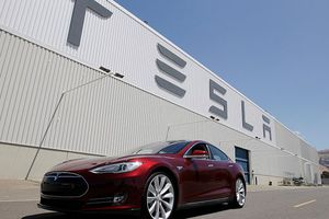 The Tesla building facade with a Model S in front.