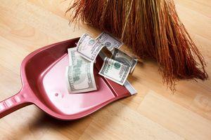 Broom sweeping dollar bills into dustbin